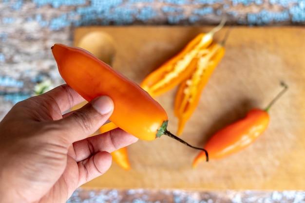 Verscheidene ajies die door mes op een keukenraad worden gehakt