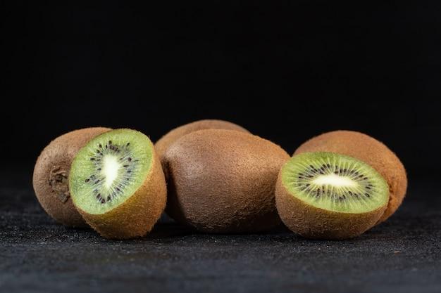 Verscheidene bruine kiwi verse rijpe sappige zachte halve besnoeiing die op donker bureau wordt geïsoleerd