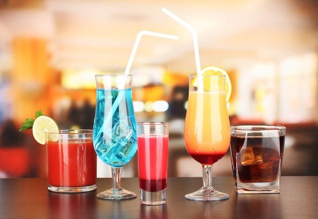 Verscheidene glazen van verschillende dranken op vage bar