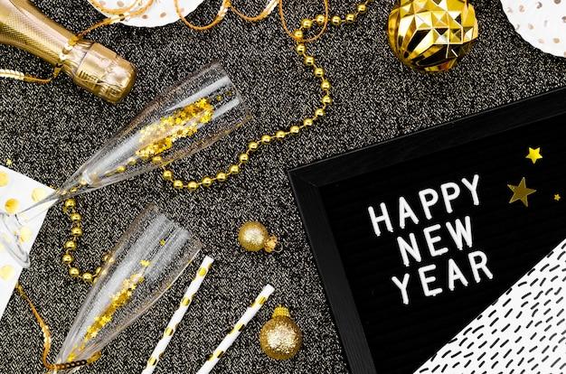 Verscheidenheid aan accessoires en glazen op zwarte achtergrond en gelukkige nieuwe jaarslinger