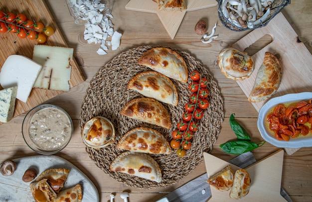 Verscheidenheid aan argentijnse zelfgemaakte empanadas op de houten tafel