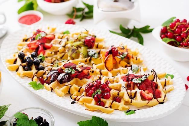 Verscheidenheid aan belgische wafels met bessen, chocolade en siroop.
