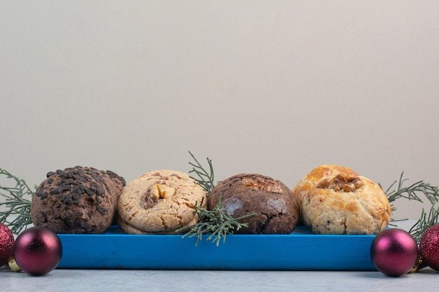 Verscheidenheid aan cookies op blauw bord met kerstballen. hoge kwaliteit foto