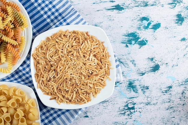 Verscheidenheid aan droge pasta op witte borden. hoge kwaliteit foto