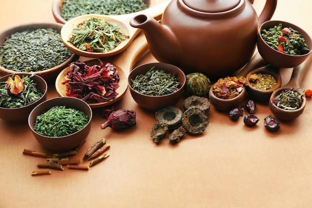 Verscheidenheid aan droge thee in kommen met theepot op lichtbruin oppervlak, close-up