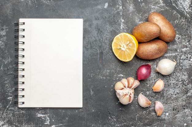 Verscheidenheid aan eten en notitieboekje op donkere achtergrond