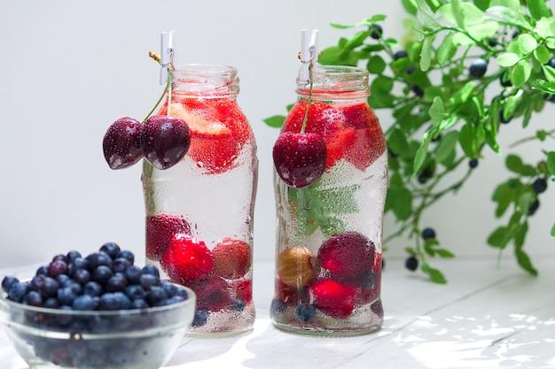 Verscheidenheid aan fruit met detox water in kleine glazen flesjes. verfrissende zomerdrankjes. gezond dieetconcept.