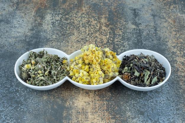 Verscheidenheid aan gedroogde bloemen en theeblaadjes in witte kommen.