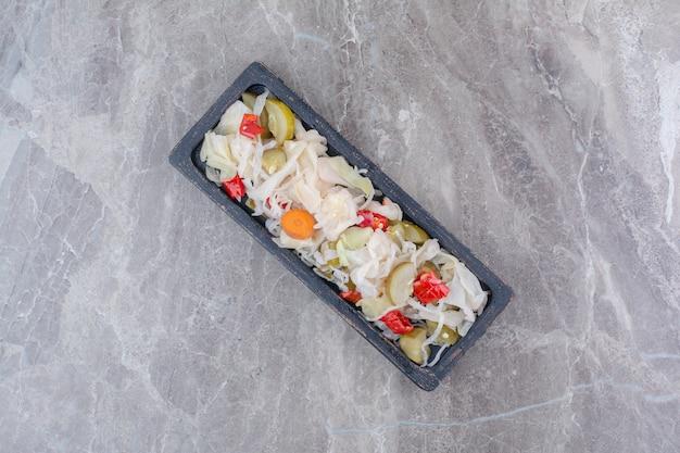 Verscheidenheid aan gehakte augurken op een donkere plaat.