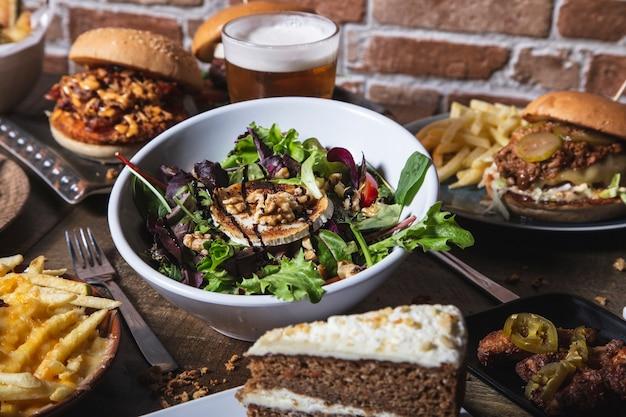 Verscheidenheid aan gerechten, salade met geitenkaas huisgemaakte hamburgers en frietjes, kippenvleugels met jalapeños drankje en cake op de houten tafel. geïsoleerde afbeelding.