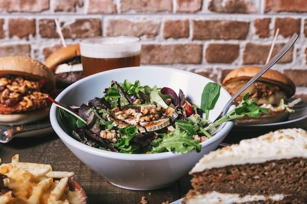 Verscheidenheid aan gerechten, salade met geitenkaas zelfgemaakte hamburgers met frietjes, drinken en cake op de houten tafel. geïsoleerde afbeelding.