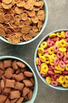 Verscheidenheid aan granen in blauwe kommen, snel ontbijt op grijze achtergrond. verticale foto