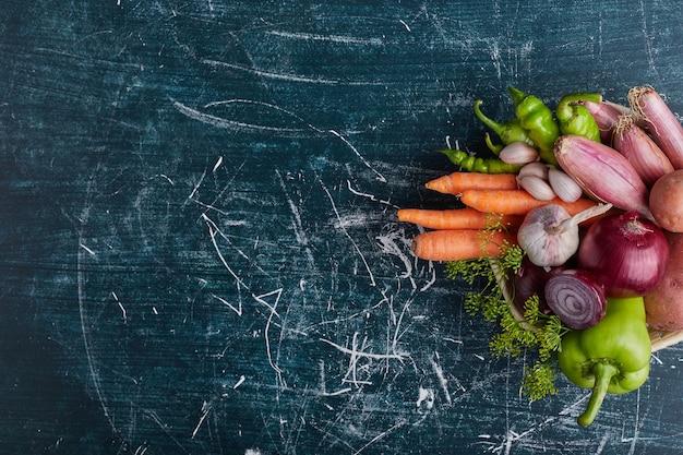 Verscheidenheid aan groenten geïsoleerd op blauwe tafel aan de rechterkant.