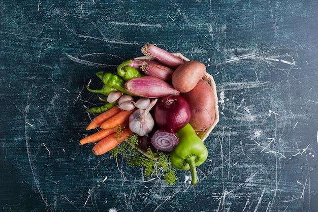 Verscheidenheid aan groenten geïsoleerd op blauwe tafel, bovenaanzicht.