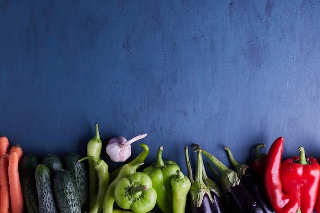 Verscheidenheid aan groenten in de bodem van blauwe tafel.
