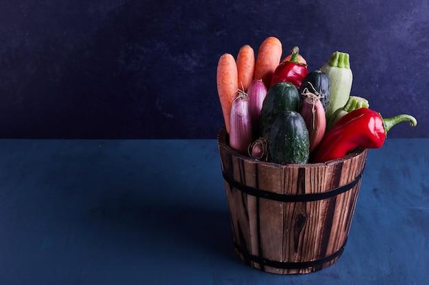 Verscheidenheid aan groenten in een rustieke emmer.
