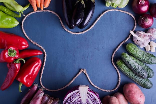 Verscheidenheid aan groenten in het frame van blauwe tafel.