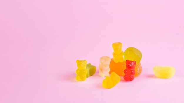 Verscheidenheid aan gummy beren snoepjes op roze achtergrond