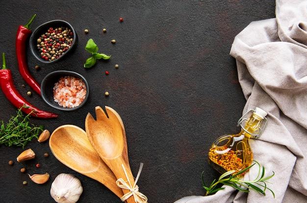 Verscheidenheid aan kleurrijke kruiden. zoutvlokken, gemengde peper, rozemarijn, basilicum en knoflook op donkere zwarte leiachtergrond. bovenaanzicht. kopieer ruimte.