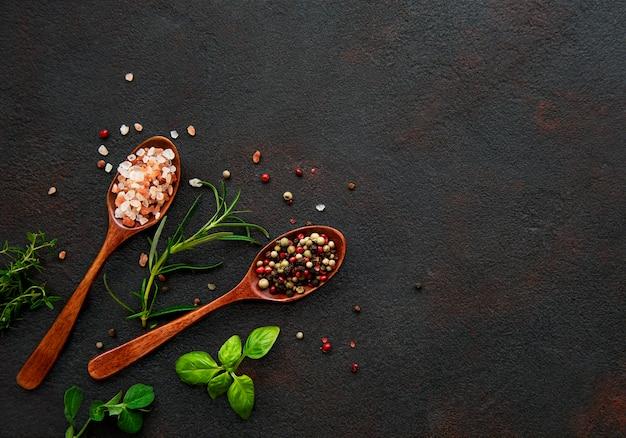 Verscheidenheid aan kleurrijke kruiden. zoutvlokken, gemengde peper, rozemarijn, basilicum en knoflook op donkere zwarte leisteentafel. bovenaanzicht. kopieer ruimte.
