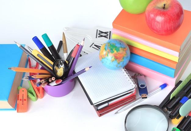 Verscheidenheid aan kleurrijke schoolbenodigdheden op een witte tafel