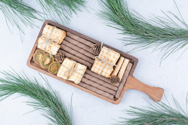 Verscheidenheid aan koekjes en gedroogde kiwi op een houten bord.