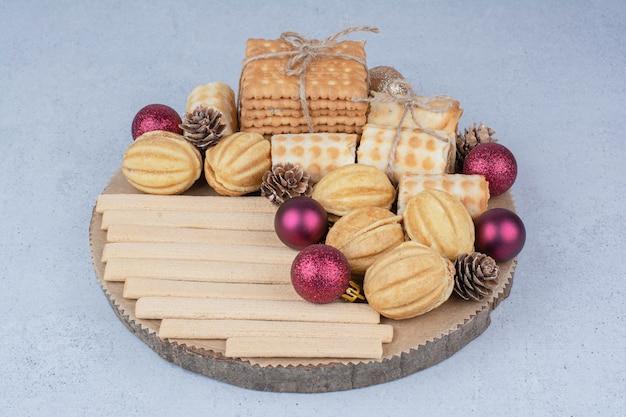 Verscheidenheid aan koekjes en kerst ornamenten op een houten bord.