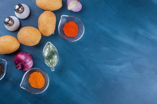 Verscheidenheid aan kruiden, aardappelen en uien op blauwe ondergrond.