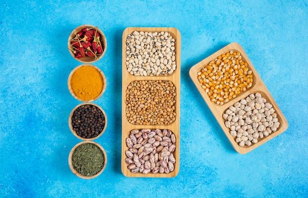 Verscheidenheid aan kruiden en rauwe bonen op blauwe ondergrond