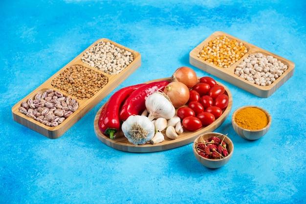 Verscheidenheid aan kruiden, groenten en rauwe bonen op blauwe achtergrond.