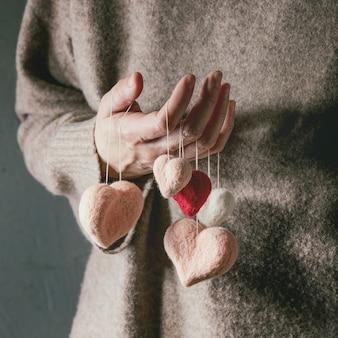 Verscheidenheid aan naaldvilten harten op draden in vrouwelijke handen. st valentijnsdag liefde zorg wenskaart