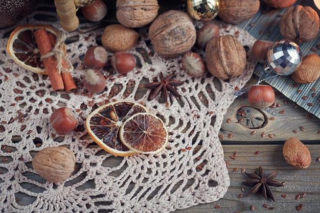 Verscheidenheid aan noten in kerst- en nieuwjaarsdecoratie. de samenstelling van kerstmis en nieuwjaar met sparrentakken, kaarsen en vakantielicht op houten achtergrond