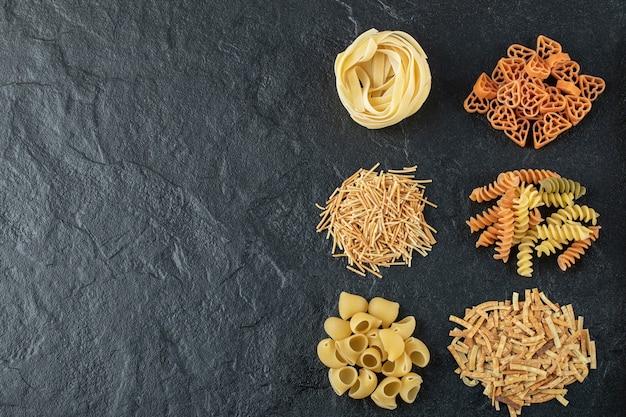 Verscheidenheid aan ongekookte pasta op zwart.