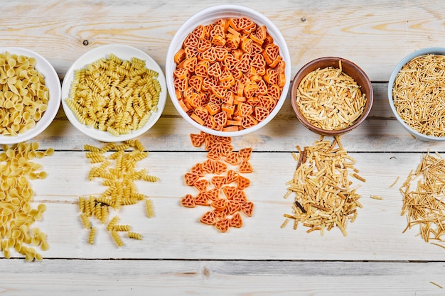 Verscheidenheid aan ongekookte pastakommen op houten tafel.