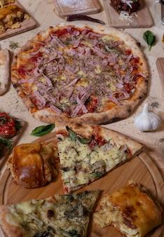 Verscheidenheid aan pizza en italiaanse tapas op houten achtergrond. geïsoleerde afbeelding. mediterrane keuken verticaal beeld