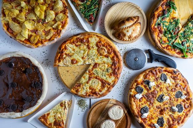Verscheidenheid aan pizza's op de tafel van het restaurant om te eten