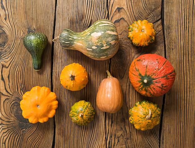 Verscheidenheid aan pompoenen op een houten achtergrond. oogst concept plat leggen.