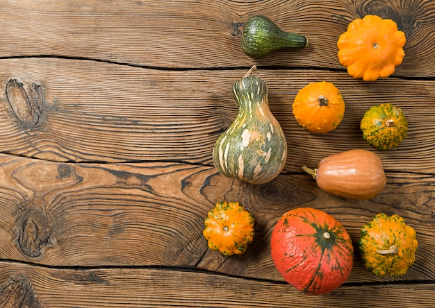 Verscheidenheid aan pompoenen op een houten achtergrond. oogstconcept plat leggen met kopie ruimte.
