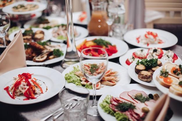 Verscheidenheid aan smakelijke koude snacks geserveerd op witte keramische platen boven een speciale gelegenheidstafel voor een bruiloftsbanket. assortiment van gekookte snacks en eten op tafel in restaurant. kerst- of nieuwjaarsviering.