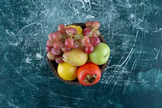 Verscheidenheid aan smakelijke vruchten in houten emmer.