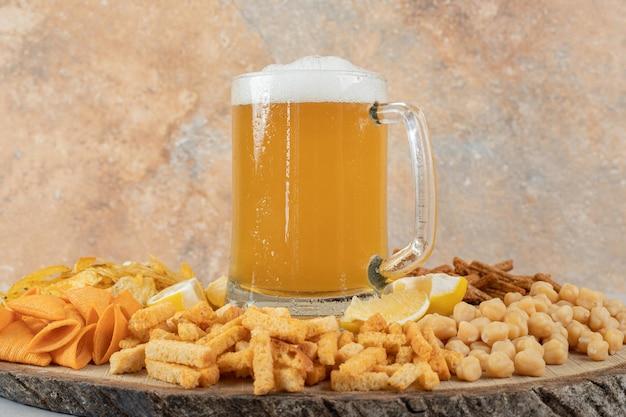Verscheidenheid aan snacks en glas bier op houten stuk