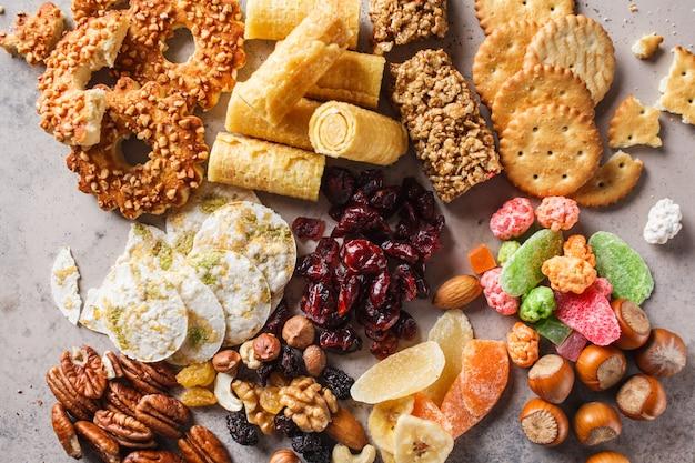 Verscheidenheid aan snacks en snoepjes op grijze achtergrond. wafels, noten, snoep, koekjes, chips en fruit, bovenaanzicht.