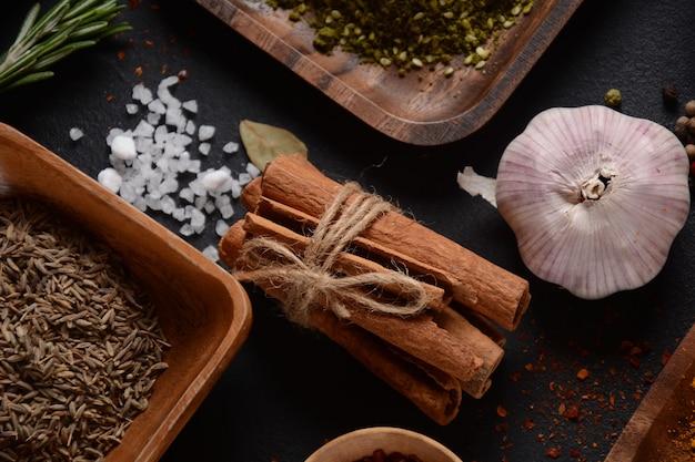 Verscheidenheid aan specerijen en kruiden op de keukentafel. chilipeperpoeder, oregano, kaneelstokjes, zout, knoflook