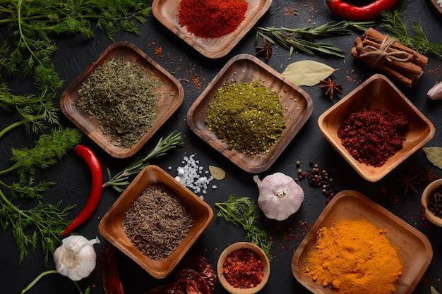 Verscheidenheid aan specerijen en kruiden op de keukentafel. kleurrijke verschillende kruiden en specerijen voor het koken op donkere achtergrond