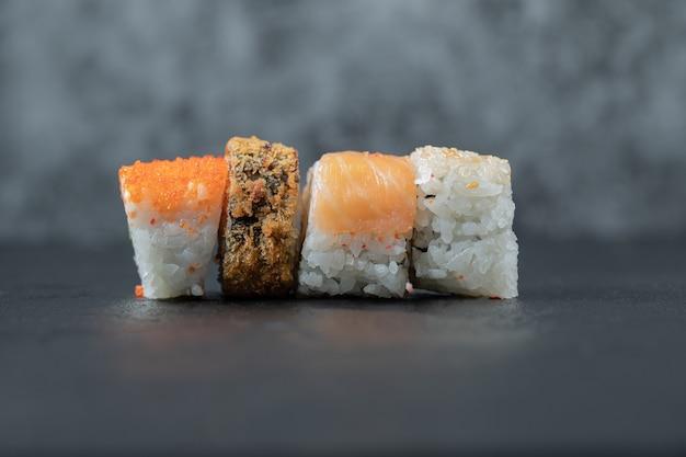 Verscheidenheid aan sushi rolt geïsoleerd op grijze tafel.