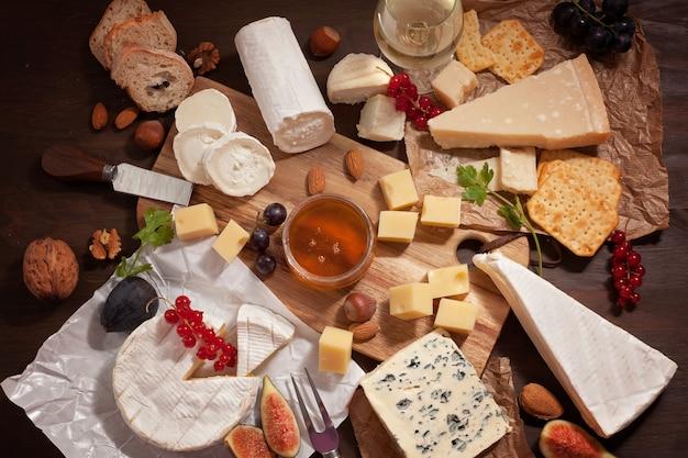 Verscheidenheid aan verschillende kaas met wijn, fruit en noten.