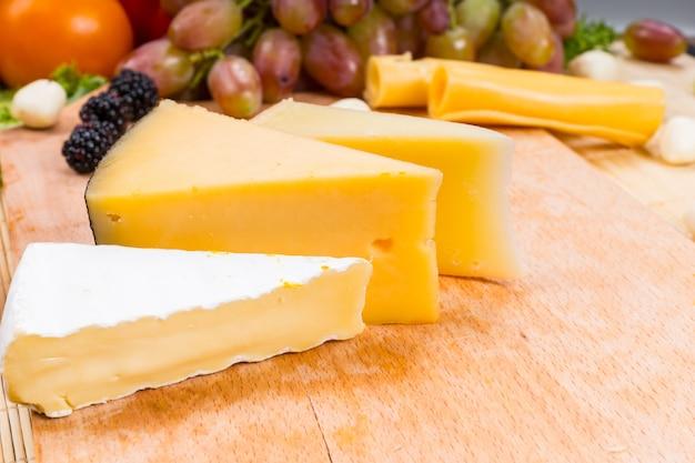 Verscheidenheid aan verschillende kaaspartjes op een houten kaasplankje met verse druiven, bramen en een tomaat op de achtergrond