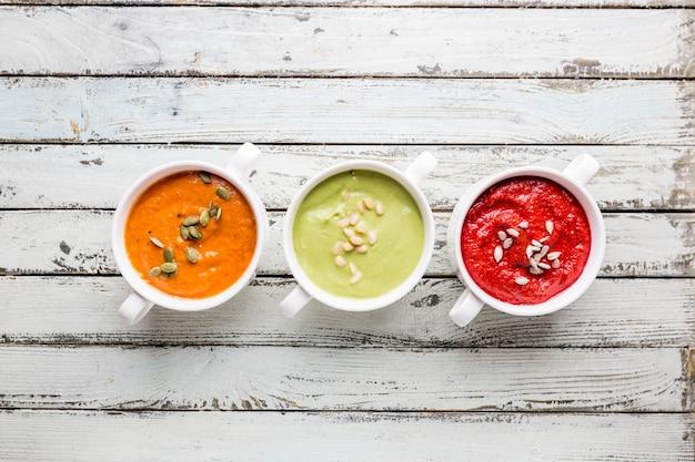 Verscheidenheid aan verschillende kleurrijke groenteroomsoepen in kommen, bovenaanzicht. concept van gezond eten of vegetarisch eten.