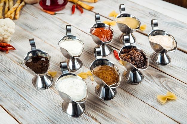 Verscheidenheid aan verschillende sauzen op de houten tafel