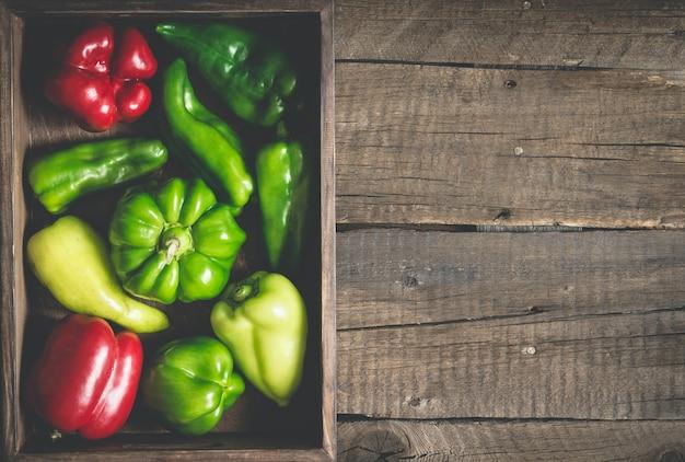 Verscheidenheid rode en groene paprika van verschillende vormen. volledige plantaardige lade op een houten achtergrond.